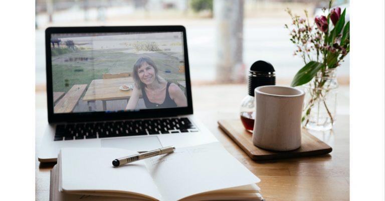 Portátil sobre escritorio con imagen de mujer en la pantalla en una seión online
