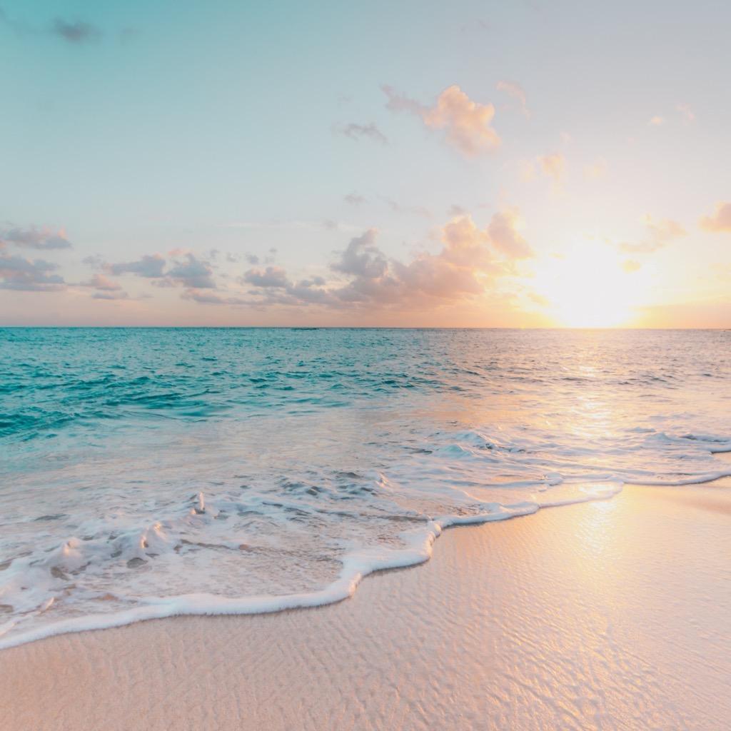 Amanecer en una playa , mar con espuma en la orilla y arena. Relación de la marea con la terapia biodinámica.